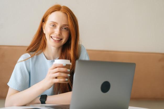 Nahaufnahmegesicht der glücklichen jungen schönen frau, die tasse mit heißem kaffee hält, der am schreibtisch mit laptop im gemütlichen café sitzt und kamera betrachtet. hübsche kaukasische dame der rothaarigen entfernt, die arbeitet oder studiert.