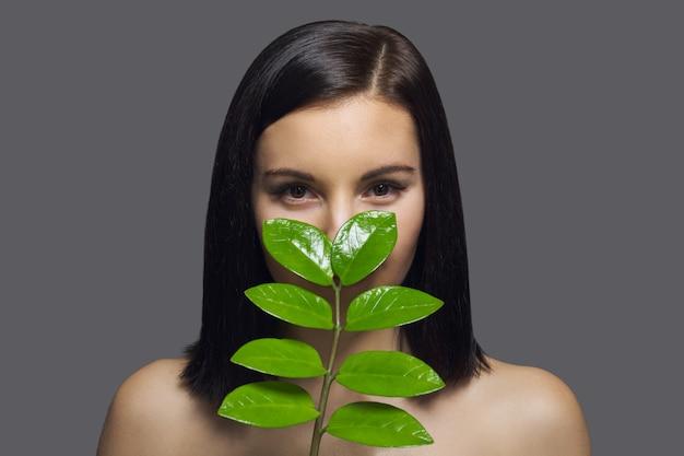 Nahaufnahmegesicht der jungen schönen frau mit grünem blatt.
