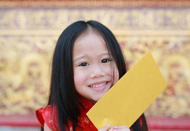 Nahaufnahmegesicht des lächelnden kleinen asiatischen mädchens, das einen goldumschlag anhält.