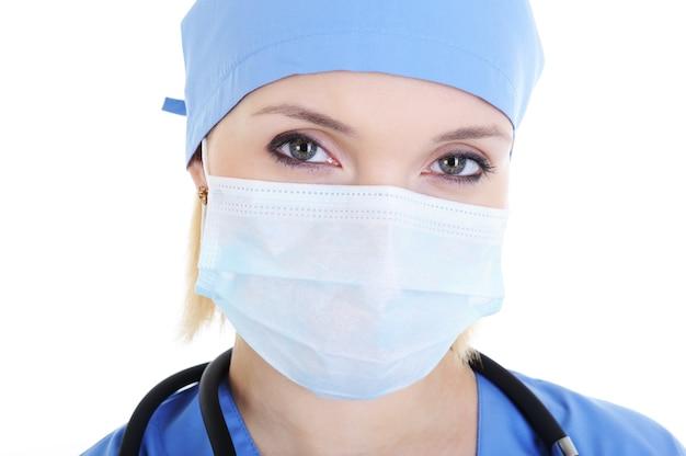 Nahaufnahmegesicht des weiblichen chirurgen in der medizinischen maske - lokalisiert auf weiß