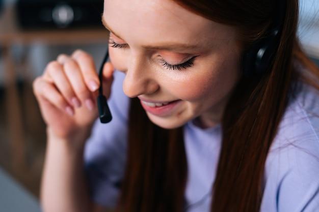 Nahaufnahmegesicht einer fröhlichen jungen operatorin, die während des kundensupports im büro ein headset verwendet