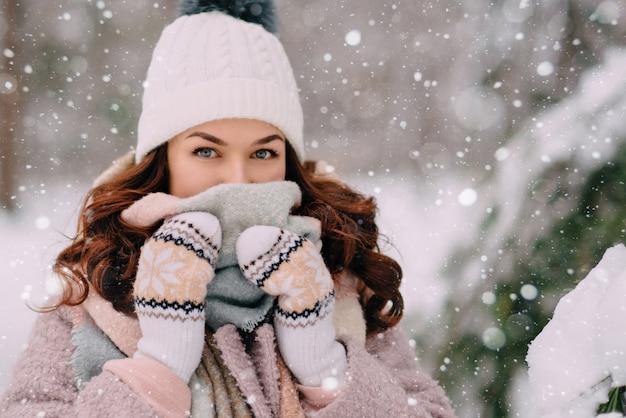 Nahaufnahmegesicht einer jungen frau, die sich in einem schal von einem schneefall versteckt