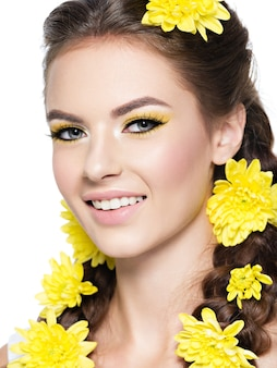 Nahaufnahmegesicht einer jungen lächelnden schönen frau mit hellgelbem make-up-modeporträt