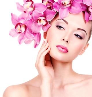 Nahaufnahmegesicht einer jungen schönen frau mit einem lila augenmake-up und lippen. hübsches erwachsenes mädchen mit blume nahe dem gesicht. - isoliert auf weißem hintergrund