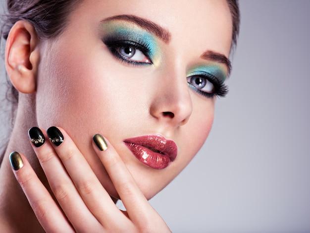 Nahaufnahmegesicht einer schönen frau mit grünem kreativem make-up
