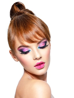 Nahaufnahmegesicht einer schönen frau mit hellem lebendigem make-up. model mit kreativem augen make-up - lokalisiert auf weiß. mädchen mit einem ingwerhaar. kurze frisur mit fransen