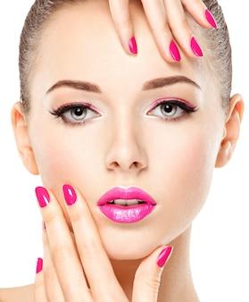 Nahaufnahmegesicht eines schönen mädchens mit rosa augen make-up und leuchtend rosa nägeln. model posiert auf weißer wand