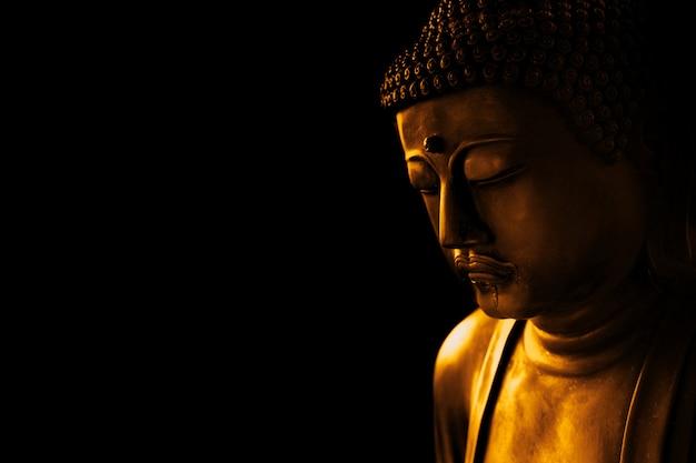 Nahaufnahmegesicht von zensteinkunst buddha in der dunkelheit für die asiatische weise des hintergrundes ruhig von der meditation und religiös.