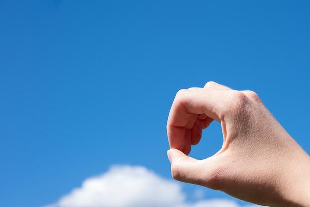 Nahaufnahmegeste der hand einer frau, die einen fingerring einzeln auf einem hintergrund des blauen himmels mit wolken macht.