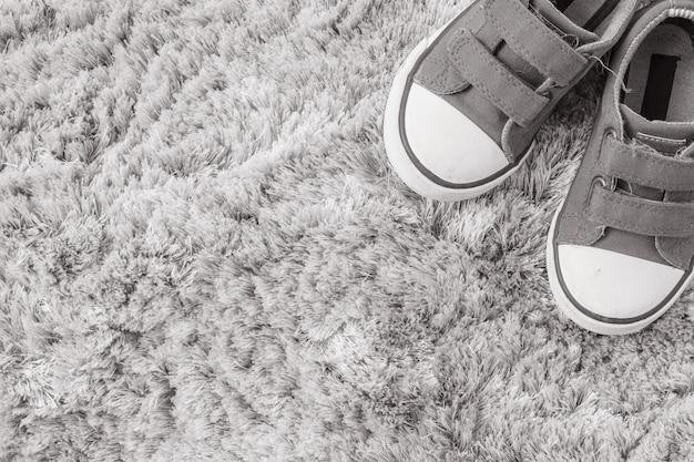Nahaufnahmegewebeturnschuhe des kindes auf grauem teppich maserten hintergrund