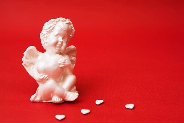 Nahaufnahmegipsengel mit einem herzen auf einer roten oberfläche. dekorativer amor zum valentinstag