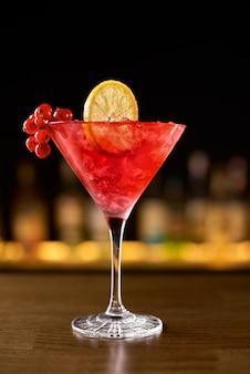 Nahaufnahmeglas kosmopolitischer cocktail verziert mit orange am barhintergrund.