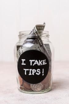 Nahaufnahmeglas mit geld als tipps