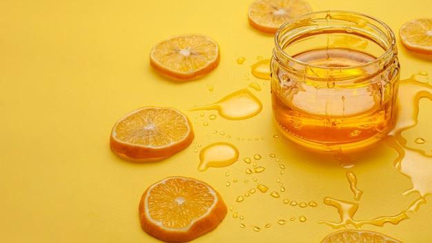 Nahaufnahmeglas mit honig und zitronen