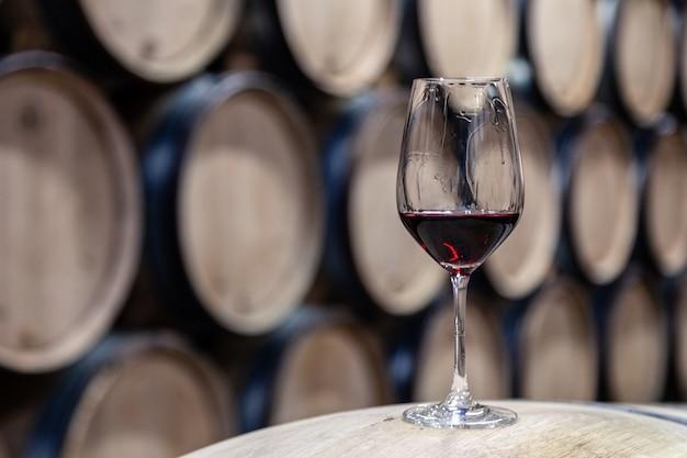 Nahaufnahmeglas mit rotwein auf dem hölzernen weineichenfaß gestapelt in den geraden reihen in der bestellung, alter keller der weinkellerei, wölbung. berufsdegustation, weinliebhaber, sommelierreisen