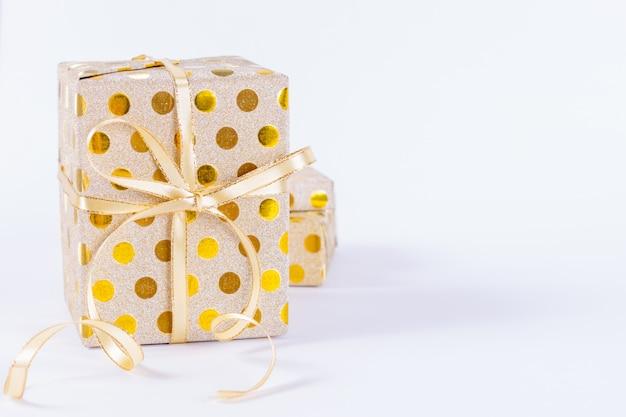 Nahaufnahmegoldgeschenkbox mit einem goldbogen auf weißem hintergrund. boxing day oder geburtstag konzept.