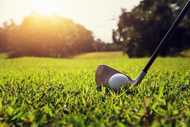 Nahaufnahmegolfclub und golfball auf grünem gras mit sonnenuntergang