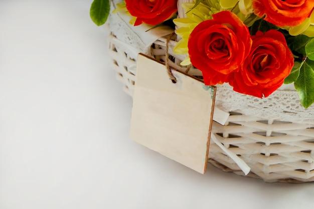 Nahaufnahmegrußkarte auf einem weißen korb mit scharlachroten rosen und gelben chrysanthemen weiß