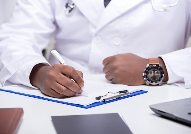 Nahaufnahmehände afrikanischen doktors sitzen bei tisch.