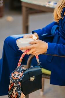Nahaufnahmehände der eleganten frau, die im café sitzt, das kaffee und stilvolle kleine geldbörse mit schal hält