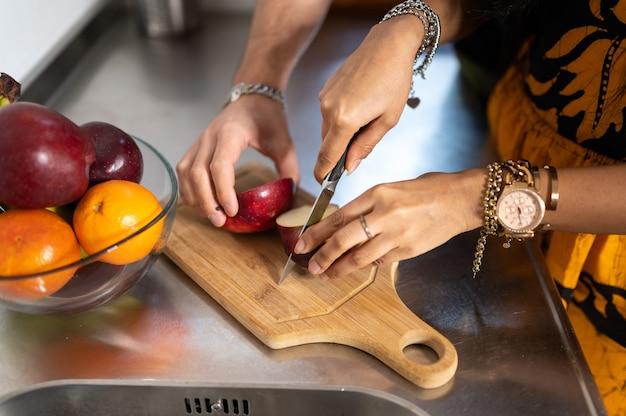 Nahaufnahmehände der frau, die einen apfel auf dem holzbrett schneidet, und mann fangen die frucht.