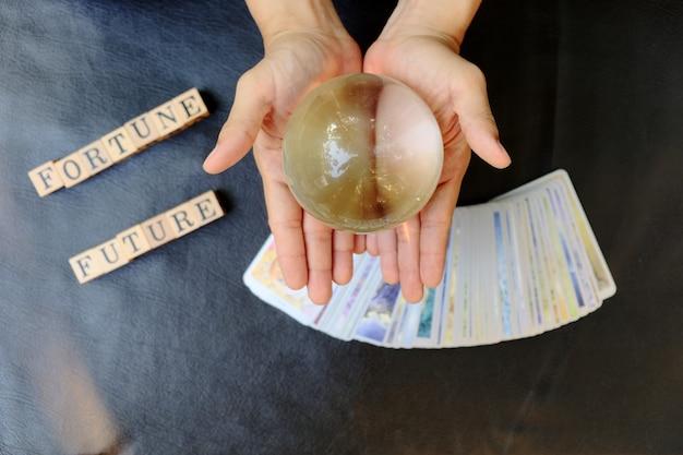 Nahaufnahmehände der wahrsagerin, die eine klare marmorkugel für die vorhersage des schicksals auf der tarotkarte zeigen