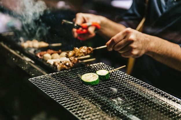 Nahaufnahmehände des japanischen yakitori-chefs, der das huhn mariniert mit ingwer, knoblauch und sojasoße und gurke mit vielem rauche grillt.