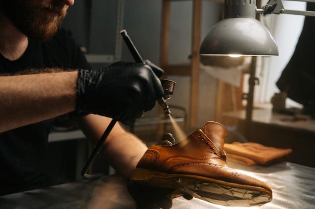 Nahaufnahmehände des schusters, der schwarze handschuhe trägt, die farbe auf lederschuhe sprühen