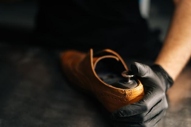 Nahaufnahmehände des schusters schuster mit schwarzen handschuhen fügt holzschuhblock in abgenutztes licht ein...
