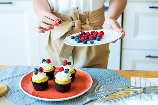Nahaufnahmehände, die cupcakes mit farbigen beeren, himbeeren und blaubeeren verzieren. lebensstil, zu hause kochen