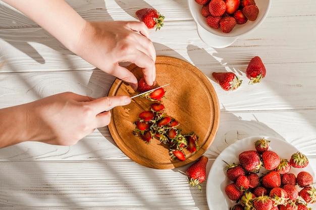 Nahaufnahmehände, die erdbeeren schneiden