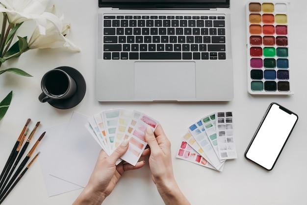 Nahaufnahmehände, die farbpalettenkarten halten