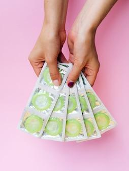 Nahaufnahmehände, die kondome mit rosa hintergrund halten