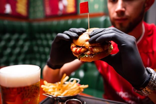 Nahaufnahmehände, die leckeren gegrillten rindfleischburger mit salat und mayonnaise halten. gruppe junger leute, die an fastfood essen. freunde verbringen zeit zusammen im café, in der bierkneipe oder in der bar.
