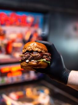 Nahaufnahmehände, die leckeren gegrillten rindfleischburger mit salat und mayonnaise halten.