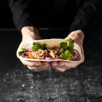 Nahaufnahmehände, die leckeren taco halten