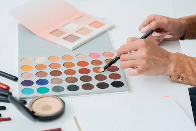 Nahaufnahmehände, die make-up versuchen