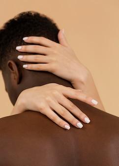 Nahaufnahmehände, die mannrückansicht halten