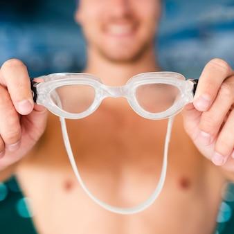 Nahaufnahmehände, die schwimmbrillen halten