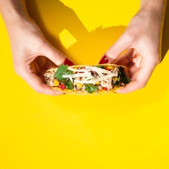 Nahaufnahmehände, die taco mit gelbem hintergrund halten