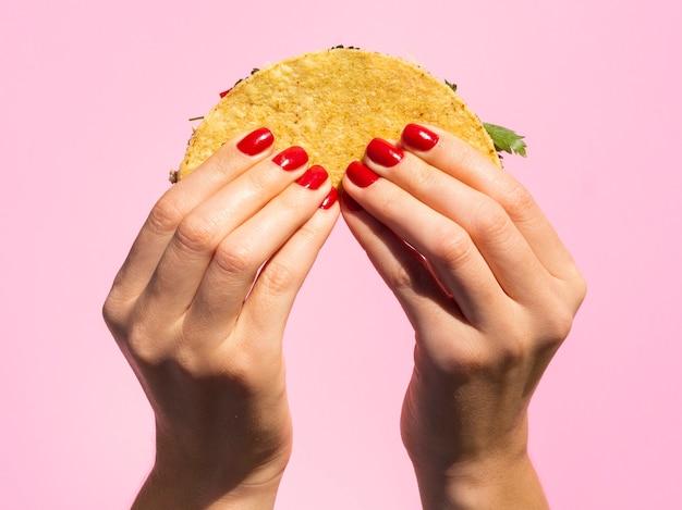 Nahaufnahmehände, die taco mit rosa hintergrund halten