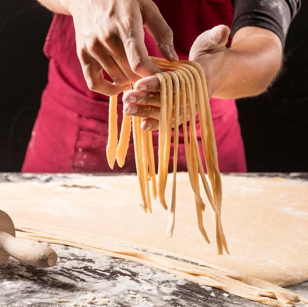 Nahaufnahmehände, die ungekochte nudeln halten