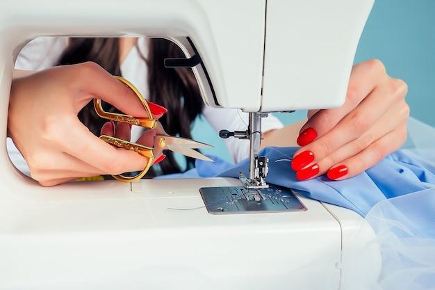 Nahaufnahmehände einer attraktiven schneiderin (schneiderin) fädeln die nadel auf die nähmaschine auf blauem hintergrund im studio. das konzept der schaffung einer neuen kleiderkollektion