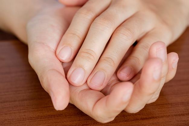 Nahaufnahmehände einer frau, deren nägel kurz und sauber geschnitten wurden. das konzept der pflege, saubere fingernägel.
