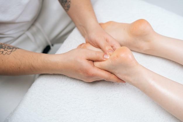 Nahaufnahmehände eines männlichen masseurs, der der jungen frau, die auf dem massagetisch im spa-salon liegt, die füße massiert