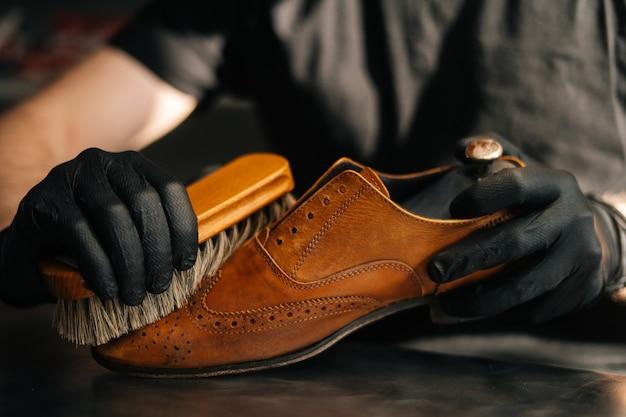 Nahaufnahmehände eines nicht erkennbaren schusters, der mit alten hellbraunen lederschuhen der bürste säubert