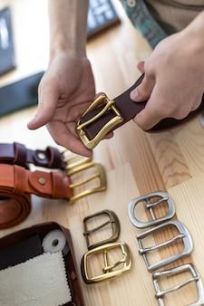 Nahaufnahmehände eines professionellen gerbers, der gürtelschnalle auf holztisch in der lederwerkstatt wählt