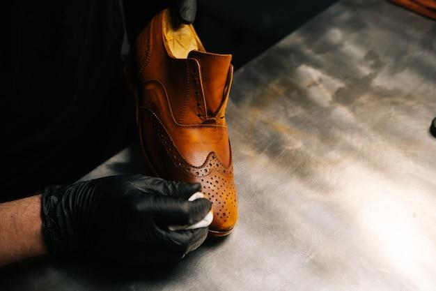 Nahaufnahmehände eines schusters, der schwarze handschuhe trägt, die farbe auf die zehenschale des hellbraunen lederschuhs reiben...