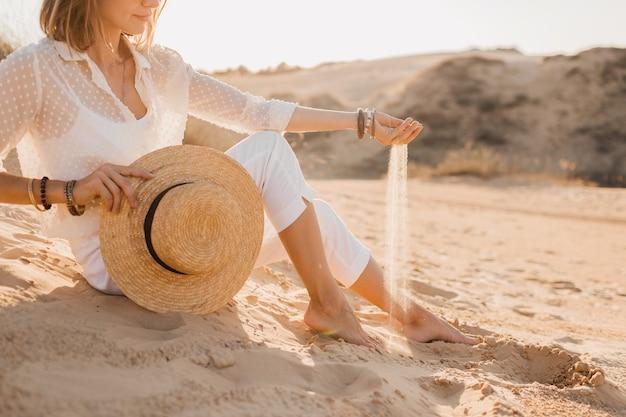 Nahaufnahmehände mit sand der stilvollen schönen frau in der wüste im weißen outfit, das strohhut auf sonnenuntergang hält