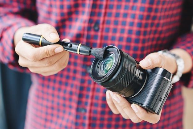 Nahaufnahmehände schossen vom berufsfotografreinigungsstaub weg vom kameraobjektiv mit bürste